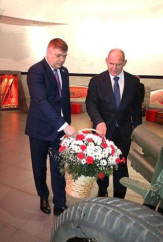 Дмитрий Василенко иАлександр Карелин вчесть павших воинов возложили корзину сцветами к76-миллиметровой полковой пушке, поднятой виюне 2020г. содна Невы